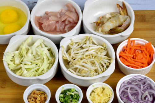 List of ingredients to cook the Singapore noodles. From top left to right bottom: eggs, chicken, shrimps, cabbage, bean sprouts, carrots, dry shrimps, scallions, garlic, onions.